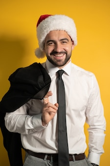 Handsome santa businessman in red santa hat wearing black suite posing holding his jacket on his shoulder, hanging it behind looking cheerful at front isolated on yellow wall