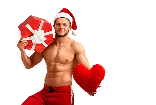 Handsome santa claus holding heart and a present
