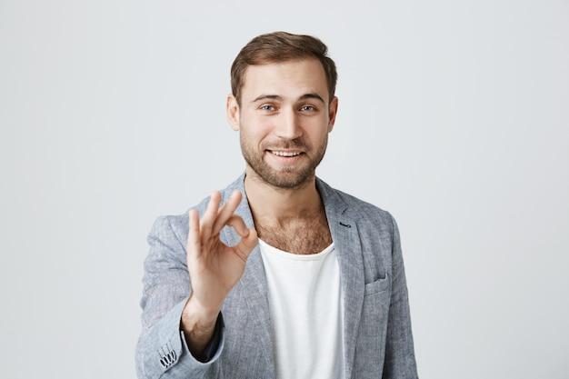 Красивый довольный бородатый мужчина показывает хорошо знаком