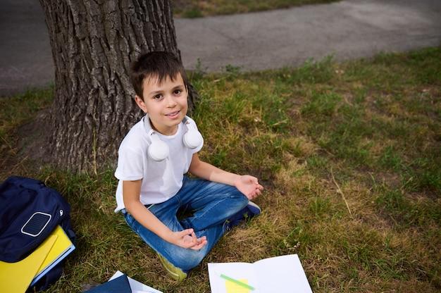 공원의 푸른 잔디에 연꽃 위치에 앉아 명상을 하고 카메라를 올려다보며 귀여운 미소를 짓고 있는 잘생긴 학교 소년. 풀밭에 누워 있는 통합 문서 및 학용품