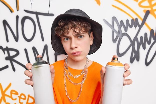 Красивый школьник очень серьезно смотрит в камеру, проводит свободное время после школы с друзьями, рисует граффити стену с помощью аэрозольных баллончиков, носит шляпу оранжевая футболка с металлическими цепями