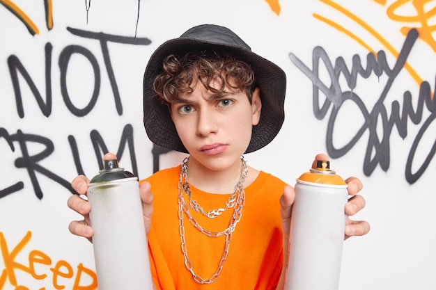 Handsome schoolboy looks very serious at camera spends free time after school with friends drawing graffiti wall with aerosol sprays wears hat orange t shirt metal chains