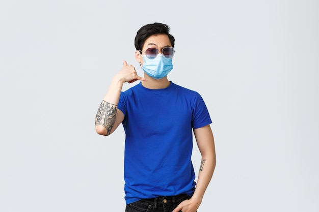Handsome self-assured young asian guy, man in sunglasses and medical mask, flirting, make phone call me sign