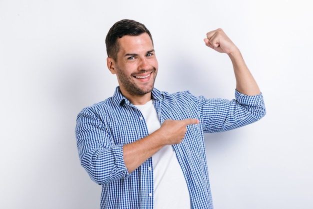 Handsome self confident man pointing finger on his arm muscle, pumping in gym, discount. indoor studio shot isolated on white background
