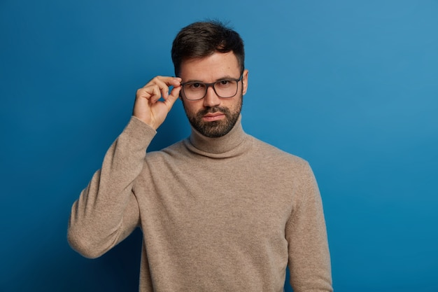 Handsome self confident man with thick bristle, keeps hand on rim of glasses