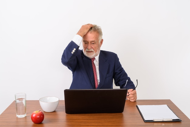 Handsome senior bearded businessman holding eyeglasses and brushing hair back while using laptop with basic things for work on wooden table on white.