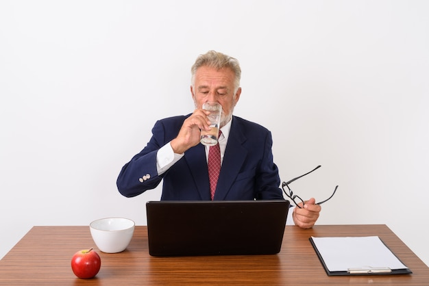 Handsome senior bearded businessman holding eyeglasses while drinking water and using laptop with basic things for work on wooden table on white.