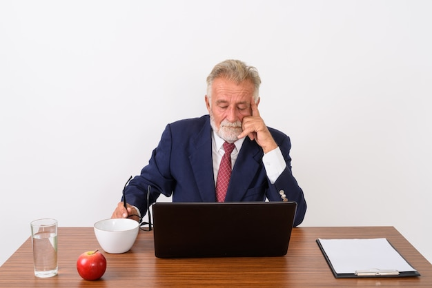 Handsome senior bearded businessman holding eyeglasses while thinking and using laptop with basic things for work on wooden table on white