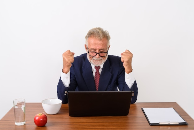Handsome senior bearded businessman looking excited while using laptop and wearing eyeglasses with basic things for work on wooden table on white.