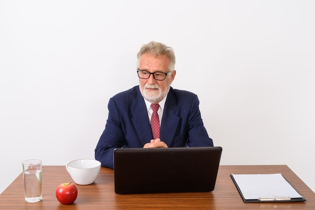 Handsome senior bearded businessman thinking while sitting with basic things for work on wooden table on white