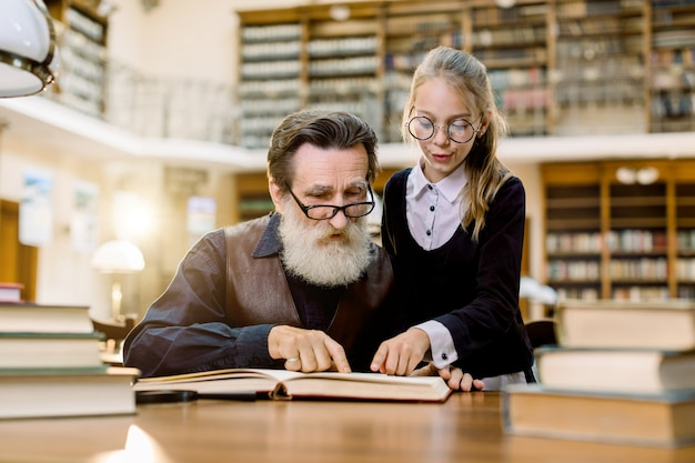 Handsome senior bearded grandfather reading book together with his cute pretty granddaughter, pointing on interesting moment in book
