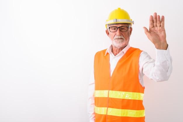 흰색에 안경을 착용하는 동안 중지 손 기호를 보여주는 잘 생긴 수석 수염 난된 남자 건설 노동자