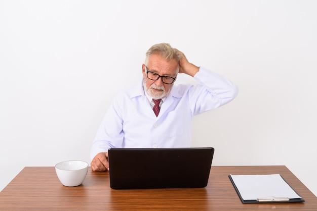 Красивый старший бородатый мужчина врач фиксирует волосы во время использования ноутбука на деревянном столе на белом
