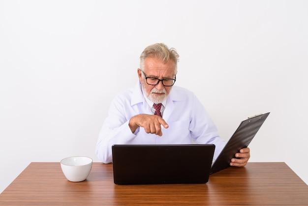 Красивый старший бородатый мужчина доктор держит буфер обмена, указывая на ноутбук на деревянном столе на белом