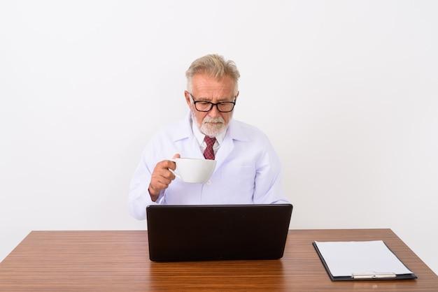 Красивый старший бородатый мужчина доктор держит чашку кофе во время использования ноутбука на деревянном столе на белом