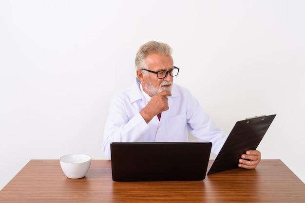 Красивый старший бородатый мужчина доктор думает во время чтения в буфер обмена с ноутбуком и чашкой кофе на деревянном столе на белом