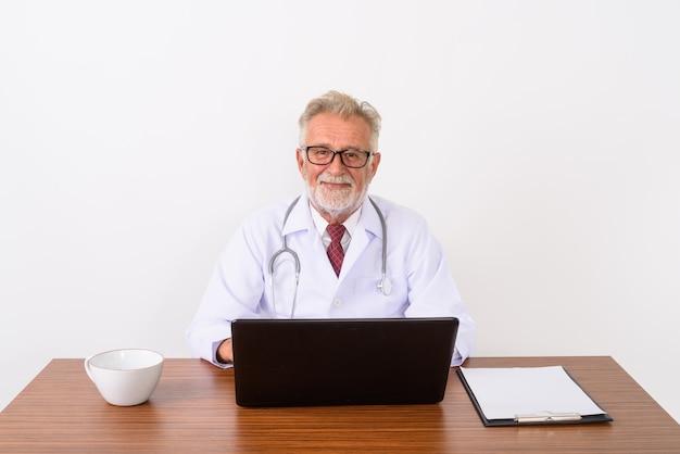 Красивый старший бородатый мужчина врач с ноутбуком на деревянном столе на белом