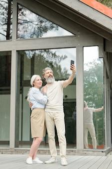 Красивый старший бородатый мужчина обнимает жену, делая селфи с ним возле стеклянного дома