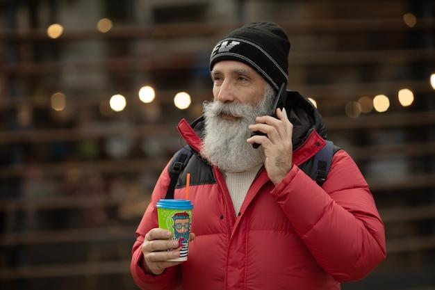 ハンサムなシニアのひげを生やした男が事務所ビルの横の通りでコーヒーブレークを持っている間、スマートフォンで話しています。