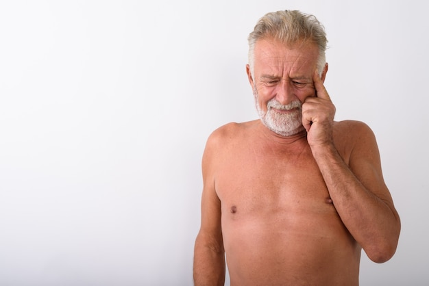 Handsome senior bearded man thinking while looking stressed shirtless on white