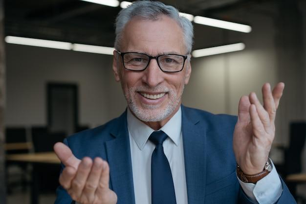 Красивый старший бизнес-тренер с видеозвонком, разговаривает в камеру, что-то объясняет