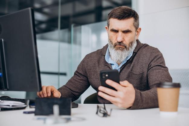 Uomo d'affari anziano bello che lavora al computer in ufficio