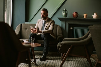 Handsome senior businessman drinking coffee and using mobile phone in lobby