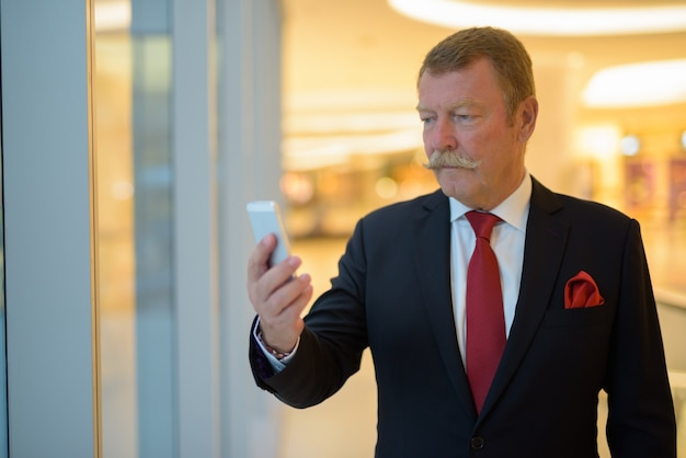 Handsome senior businessman with mustache using phone in the city
