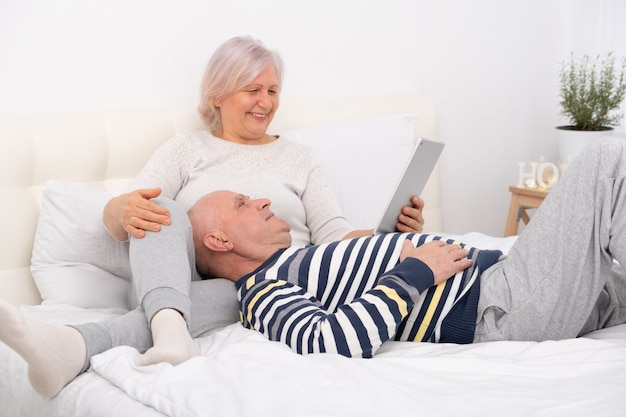 Handsome senior couple lying in bed watching tablet at home