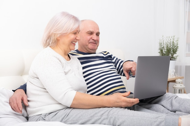 ハンサムな年配のカップルの女性と男性が自宅でラップトップを使用してベッドに座っています。