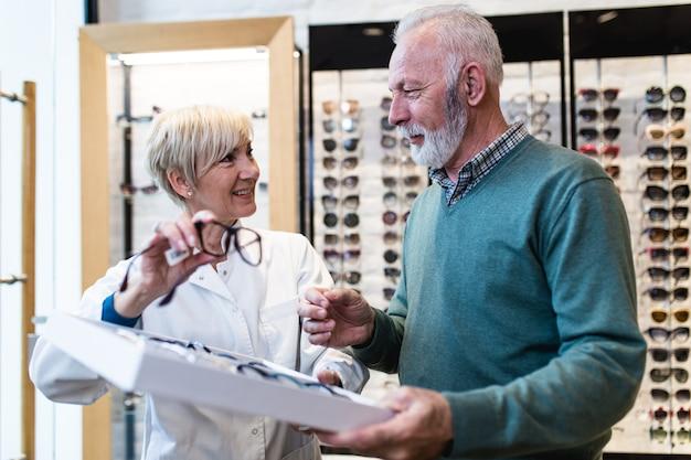 光学店で眼鏡フレームを選ぶハンサムな年配の男性。