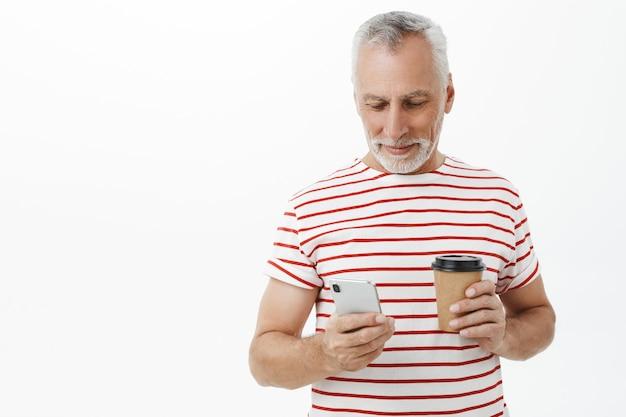 Красивый старший мужчина, отец смотрит на смартфон и пьет кофе
