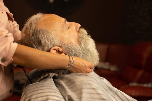 Красивый старший человек получает укладку и подстригать бороду в парикмахерской.
