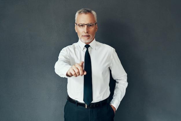 Красивый старший мужчина в элегантной рубашке и галстуке смотрит в камеру и указывает вам, стоя на сером фоне