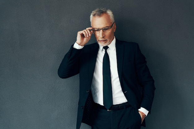 Красивый старший мужчина в полном костюме поправляет очки, стоя на сером фоне