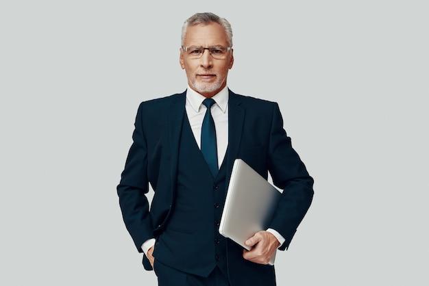 Красивый старший мужчина в полном костюме, несущий ноутбук и смотрящий в камеру, стоя на сером фоне