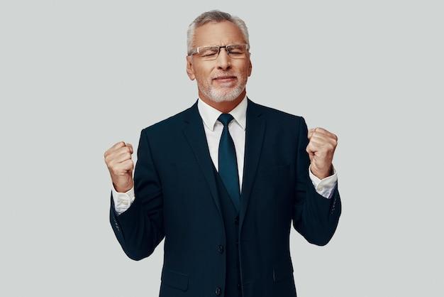 Красивый старший мужчина в полном костюме жестикулирует и аплодирует, стоя на сером фоне