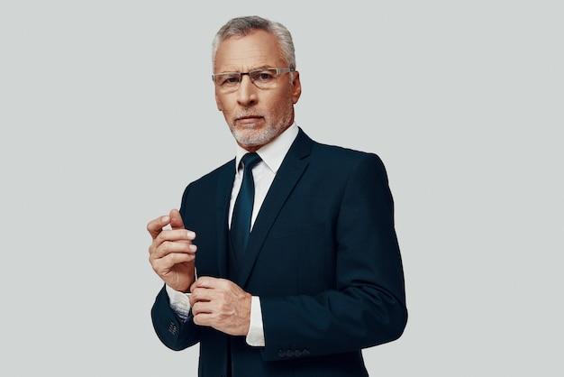 Красивый старший мужчина в полном костюме смотрит в камеру и регулирует рукав, стоя на сером фоне
