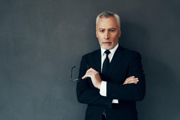 Красивый старший мужчина в полном костюме смотрит в камеру и держит скрещенными руками, стоя на сером фоне
