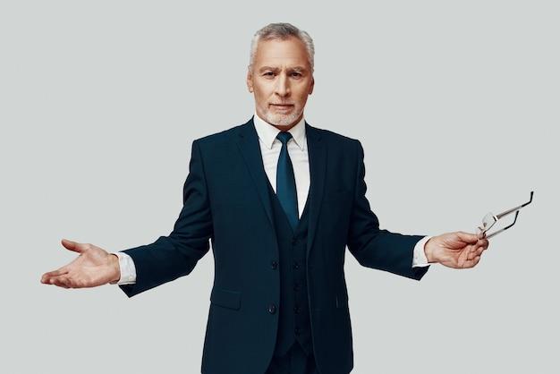 Красивый старший мужчина в полном костюме смотрит в камеру и держит вытянутые руки, стоя на сером фоне