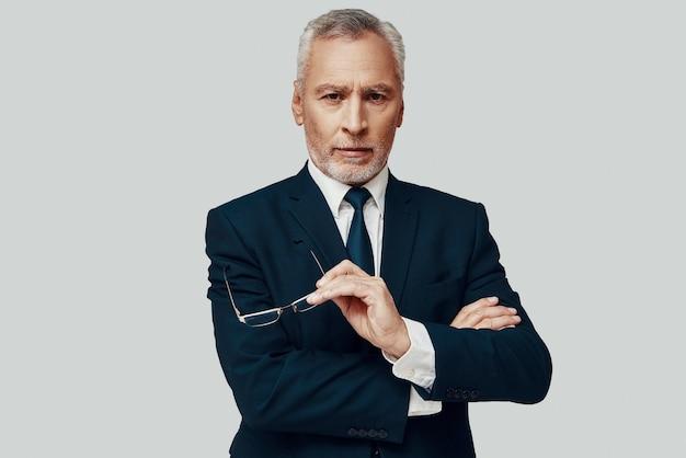 Красивый старший мужчина в полном костюме смотрит в камеру и держит руку на подбородке, стоя на сером фоне