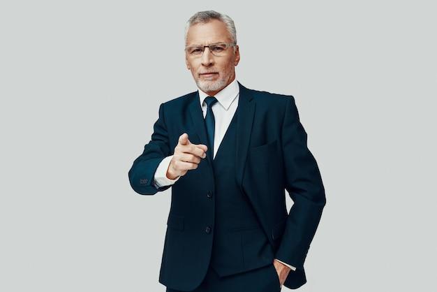 Красивый старший мужчина в полном костюме смотрит в камеру и указывает вам, стоя на сером фоне