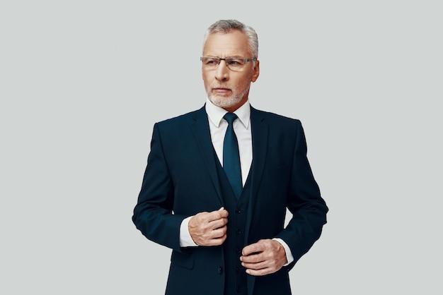 Красивый старший мужчина в полном костюме смотрит в сторону и поправляет костюм, стоя на сером фоне