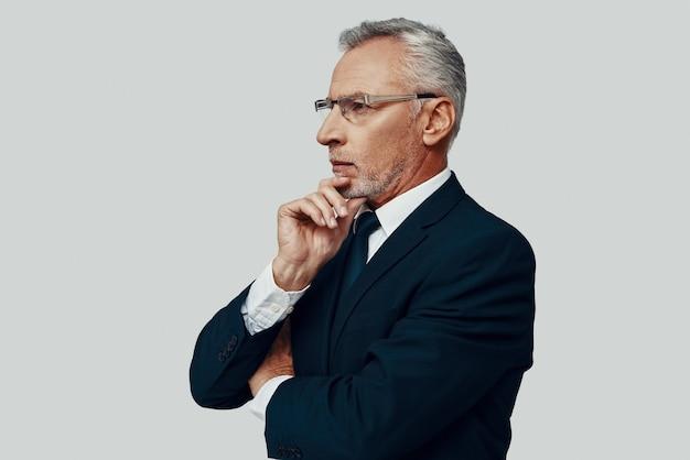Красивый старший мужчина в полном костюме смотрит в сторону и держит руку на подбородке, стоя на сером фоне