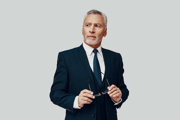 Красивый старший мужчина в полном костюме, глядя в сторону, стоя на сером фоне