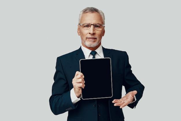 Красивый старший мужчина в полном костюме, указывая копией пространства на цифровом планшете и улыбаясь, стоя на сером фоне