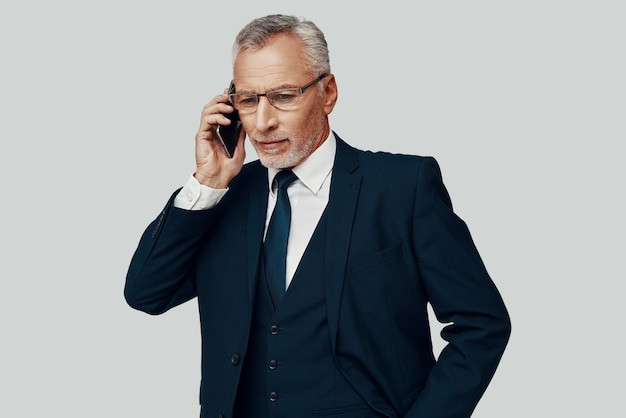 Красивый старший мужчина в полном костюме разговаривает по телефону, стоя на сером фоне