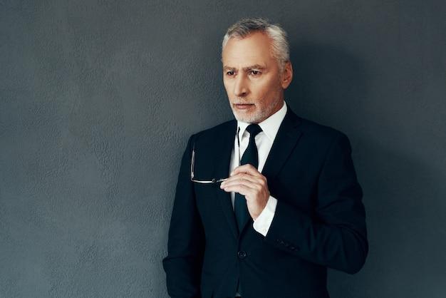 Красивый старший мужчина в полном костюме думает о чем-то, стоя на сером фоне
