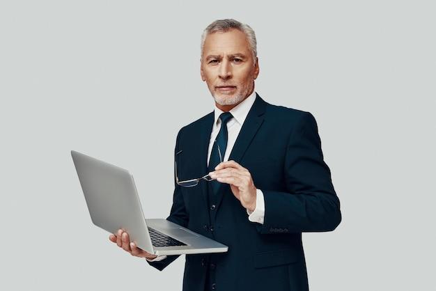 Красивый старший мужчина в полном костюме, используя ноутбук и глядя в камеру, стоя на сером фоне
