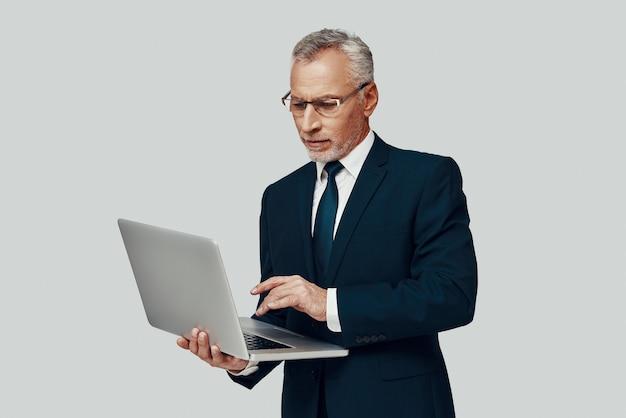 Красивый старший мужчина в полном костюме, используя ноутбук, стоя на сером фоне